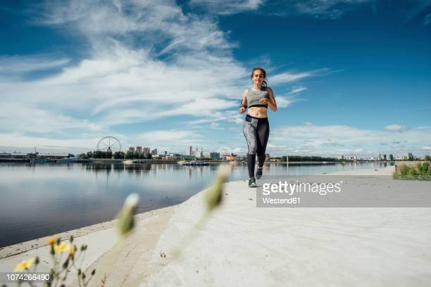 young athletic woman running at the riverside - forward athlete stock pictures, royalty-free photos & images