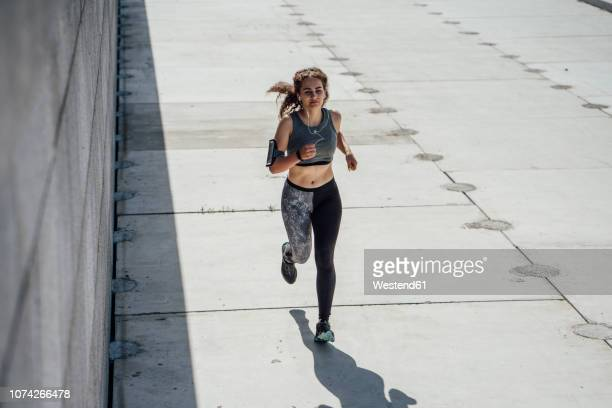 young athletic woman running on a promenade - forward athlete stock pictures, royalty-free photos & images