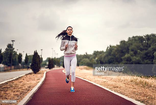 Young athletic woman running on sports track.