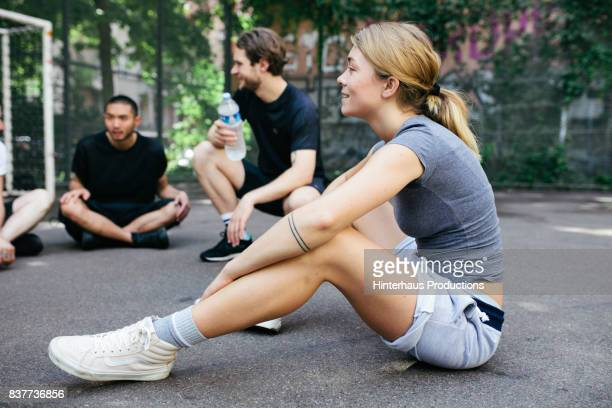 Young Athletic Woman Sitting Down With Friends To Take A Break From Outdoor Basketball Match