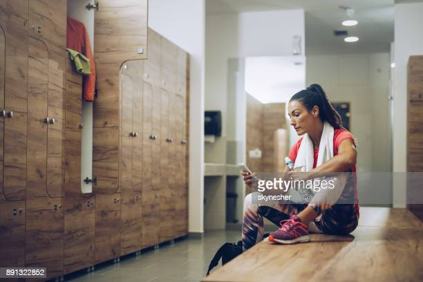 young athletic woman sitting on a bench in dressing room and using smart phone. - locker room stock pictures, royalty-free photos & images