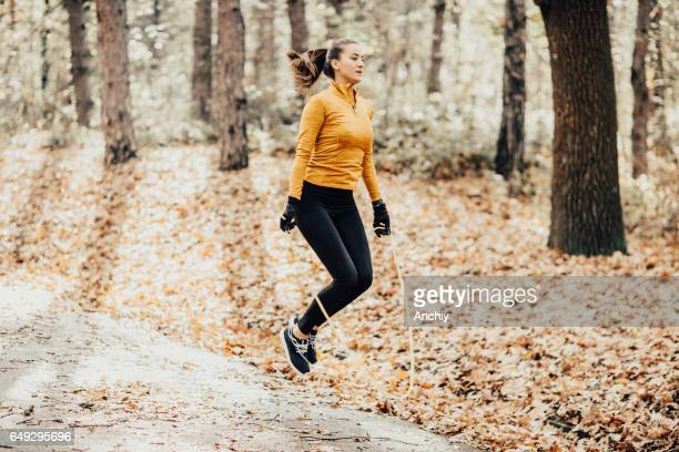 young athletic woman skipping rope in the park - skipping along stock photos and pictures