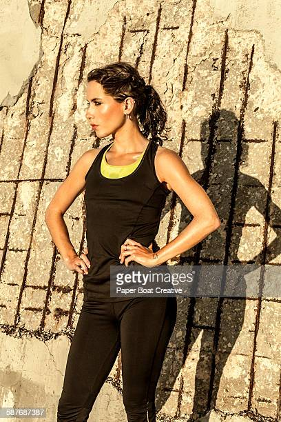 young athletic woman standing by the wall - harriet stock photos and pictures