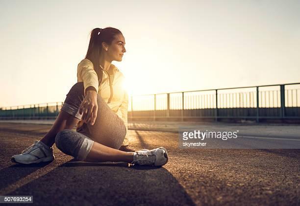 Athlétique jeune femme détente sur une route au coucher de soleil.