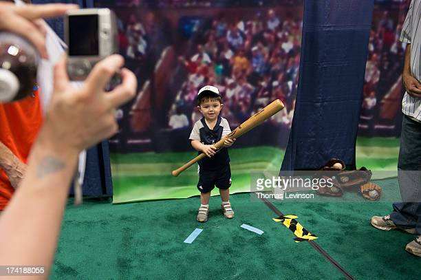 A young attendee has his picture taken for his own baseball card to be made at the Opening Day of TMobile AllStar FanFest at the Jacob K Javits...