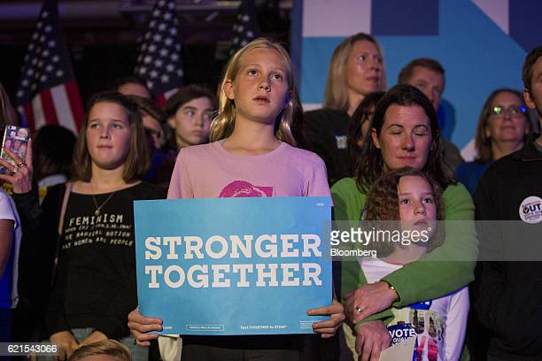 A young attendee holds a sign as musician James Taylor performs during a campaign rally for Hillary Clinton 2016 Democratic presidential nominee in...