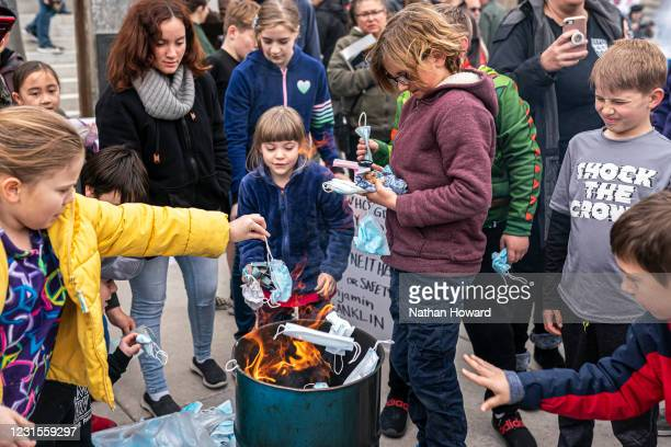 Young attendees toss surgical masks into a fire during a mask burning event at the Idaho Statehouse on March 6, 2021 in Boise, Idaho. Citizens and...