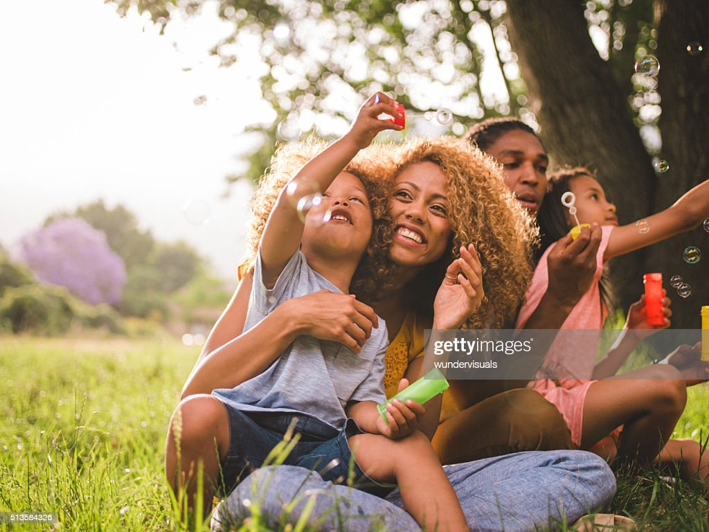 Young attractive african american family blowing bubbles in the : Stock Photo