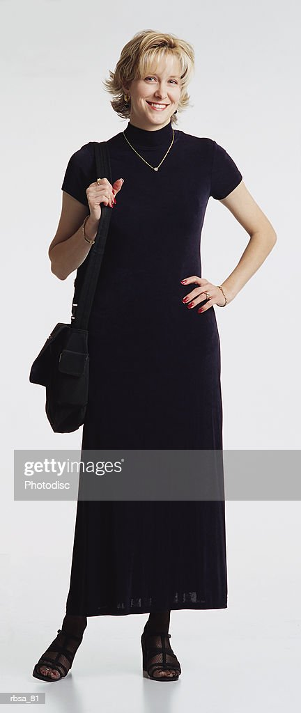 young attractive blonde caucasian thin female adult wearing a long dark dress and a diamond necklace stands as she holds a large purse on her right shoulder and looks at the camera smiling : Foto de stock