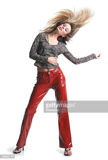 young attractive blonde caucasian woman in red leather pants dances and playfully tosses her hair