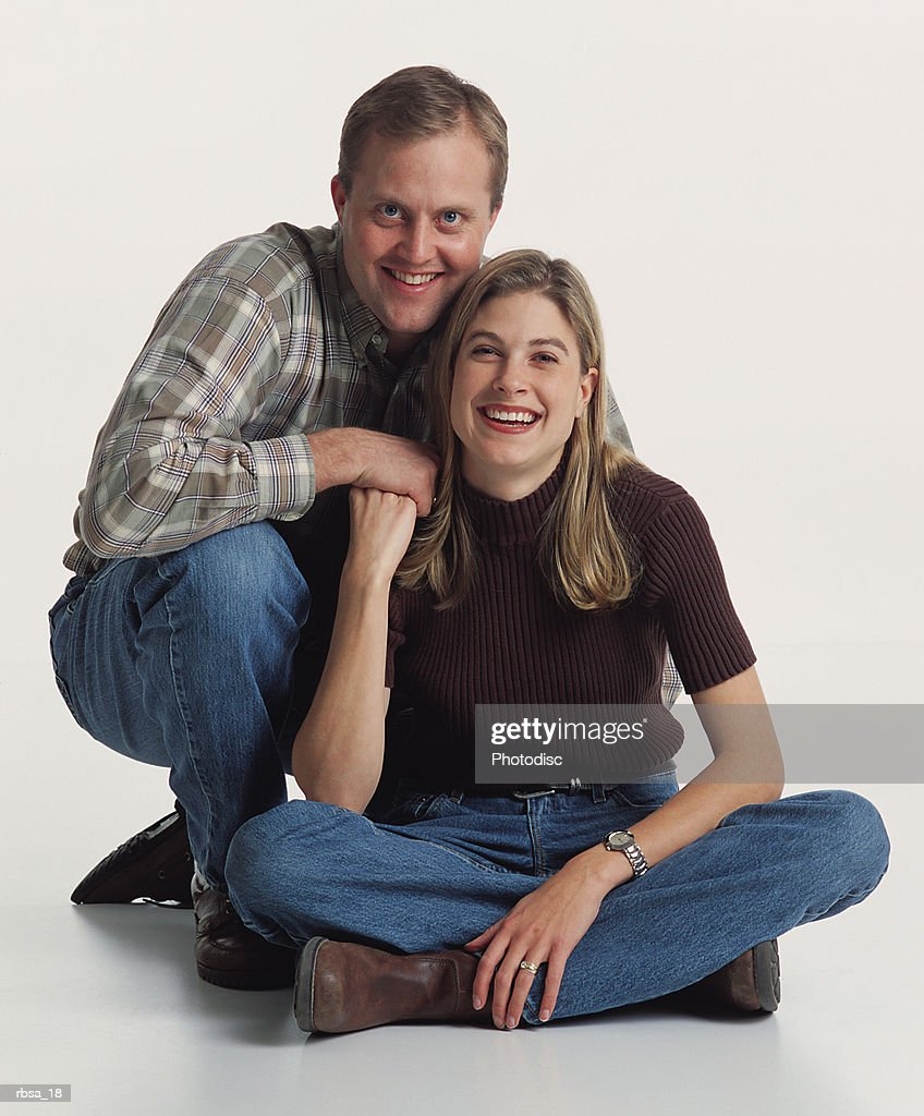 young attractive caucasian male and female couple kneel and sit on the floor wearing casual clothes while smiling happily at the camera and holding hands : Foto de stock