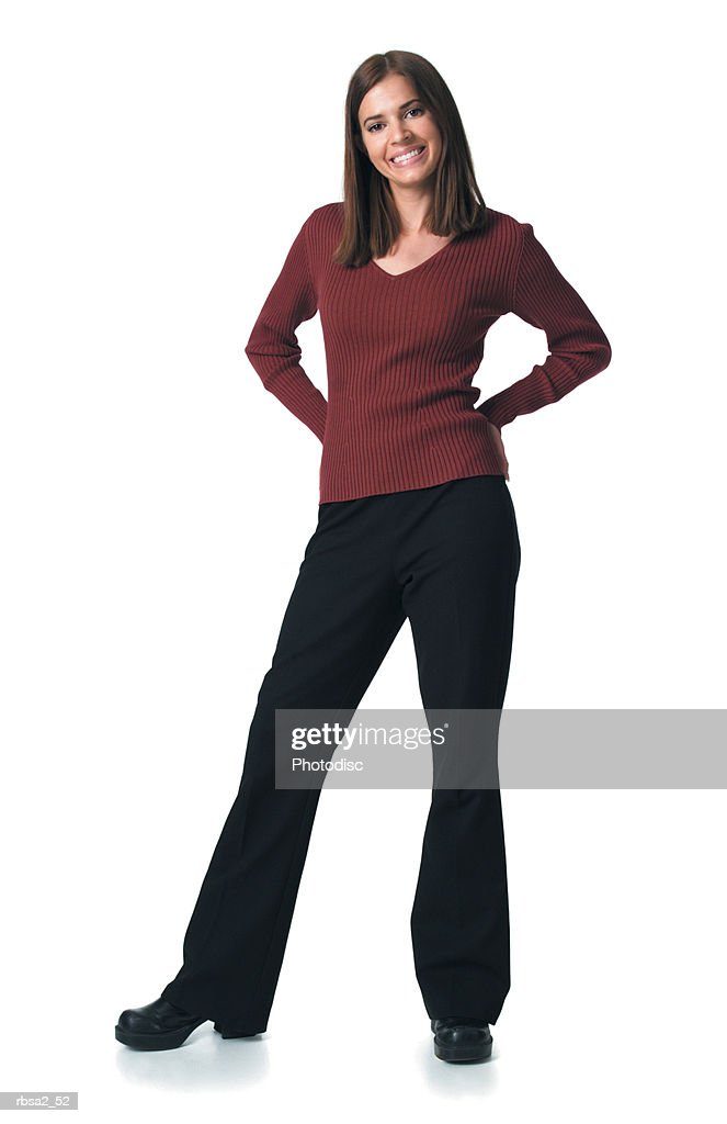 young attractive caucasian woman in black pants and red sweater puts her hand on her hips smiles : Foto de stock