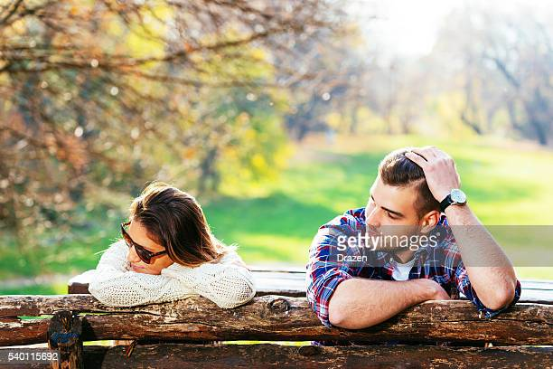 Young attractive couple having relationship issues in park
