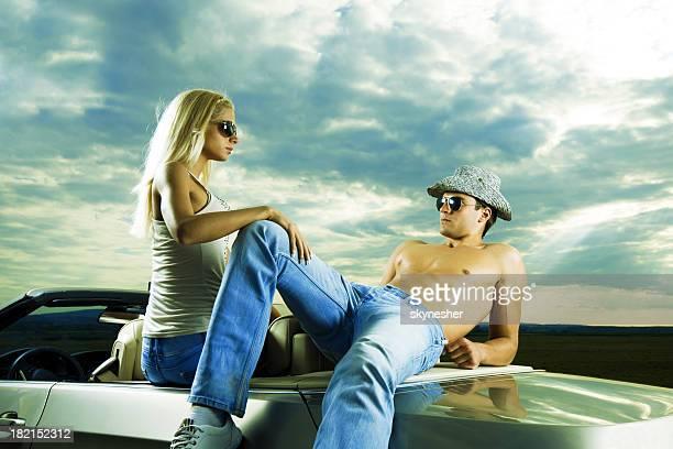 Atractiva pareja joven sentado en su coche contra las nubes.