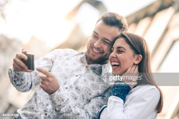 Young Attractive Couple with Smartphone Smiling at City Street