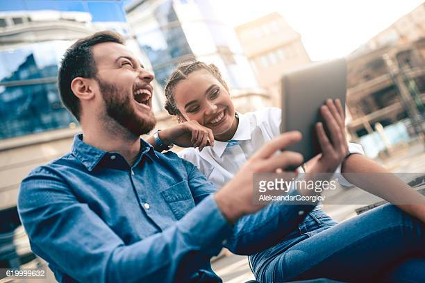 Young Attractive Couple with Tablet Laughing on City Street