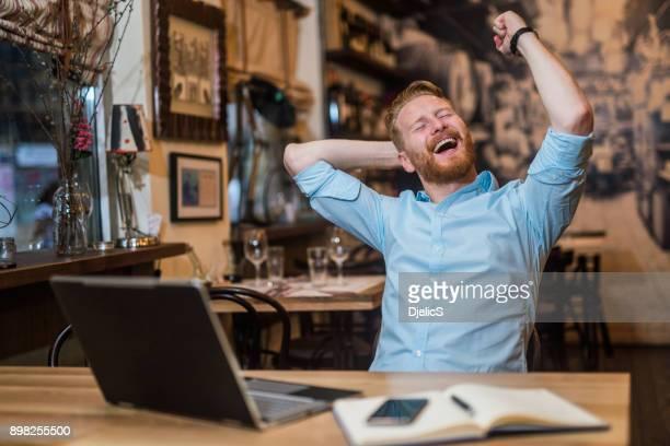 Young attractive entrepreneur celebrating his success.