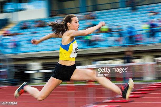 young attractive female athlete at triple jump, pannig shot - women's track stock pictures, royalty-free photos & images