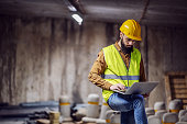 Young attractive focused bearded supervisor in vest with helmet on head standing inside of underground parking lot in construction process and using laptop.
