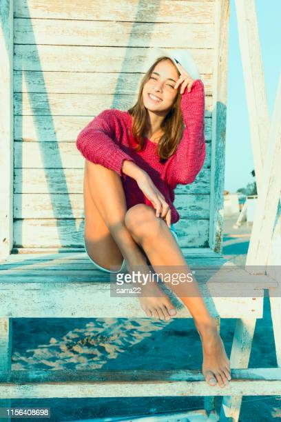 young attractive girl posing smiles at a lifeguard tower. red sweater and hat. - hot body girls stock photos and pictures