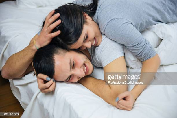 Young attractive happy amorous couple at bedroom.