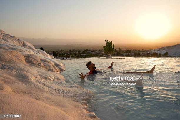 young attractive man having fun in travertines pools and terraces, pamukkale, hierapolis, golden hour in turkey at sunset time. - トラバーチン ストックフォトと画像