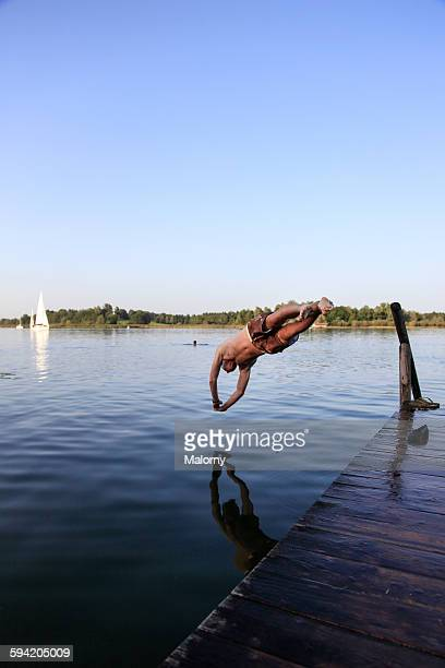 A young attractive man jumping into lake Chiemsee