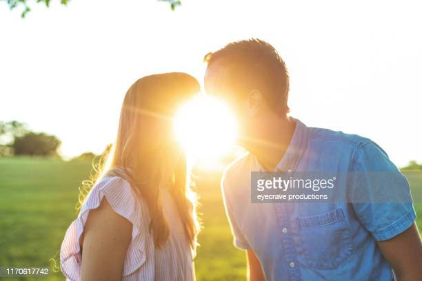 Young Attractive Millennial Married Couple in public park setting with lush green grass at golden hour in Springfield Missouri