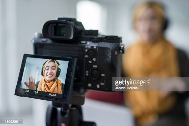young attractive muslim woman blogger or vlogger looking at camera and talking on video shooting with technology. social media influencer people or content maker concept in relax casual style at home. - live event stock pictures, royalty-free photos & images