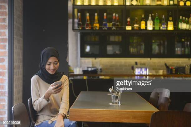 Young attractive Muslim woman in black hijab social networking at a restaurant on his cell phone or sending a text message at a cafe