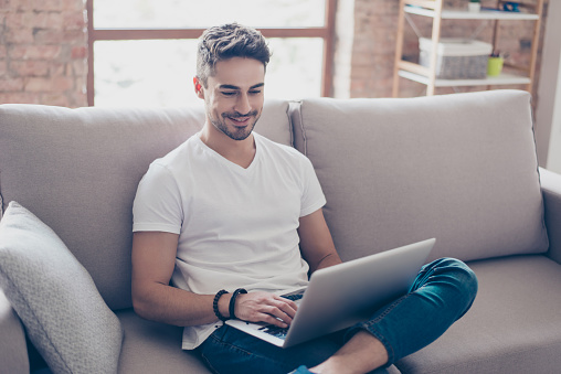 Young attractive smiling guy is browsing at his laptop, sitting at home on the cozy beige sofa at home, wearing casual outfit 939260554