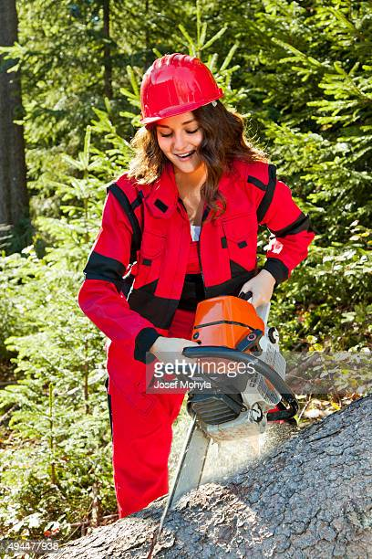 Young attractive woman as lumberjack with chainsaw