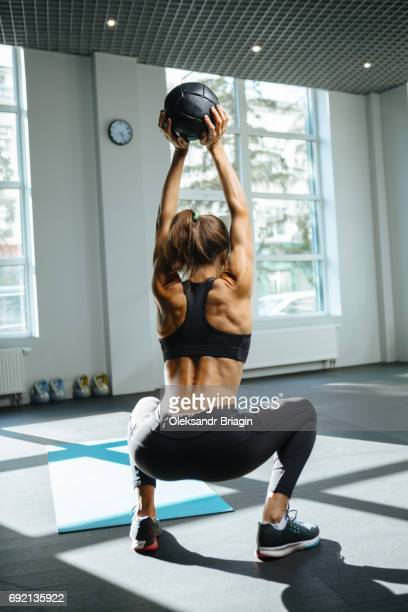 Young attractive woman exercising with medicine ball