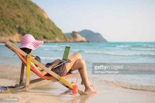 young attractive woman in dress, sunglasses and hat, working in laptop on the beach - nomadic people stock pictures, royalty-free photos & images