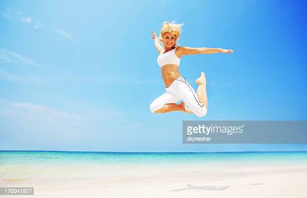 Junge attraktive Frau springen am Strand.