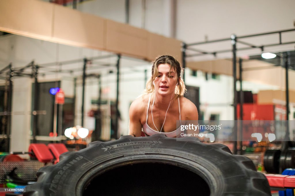 Young attractive woman lifting up a tractor tire : Stock Photo