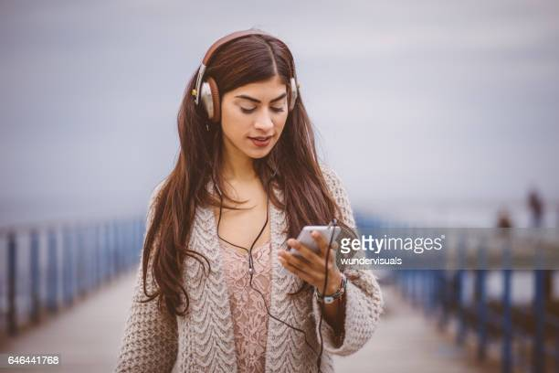 Young attractive woman listening to a podcast on her headphones