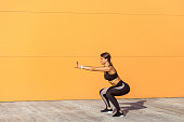 Young attractive woman practicing fitness, doing bodyweight squat exercise, yoga chair pose, working out, wearing black sportswear black pants and top,
