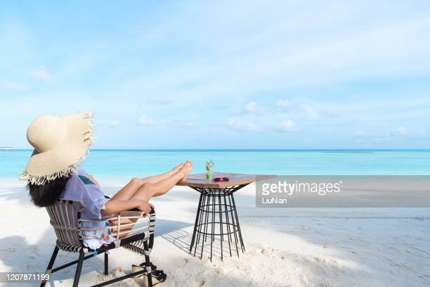 young attractive woman relaxing at seaside and looking the turquoise ocean - liu he stock pictures, royalty-free photos & images