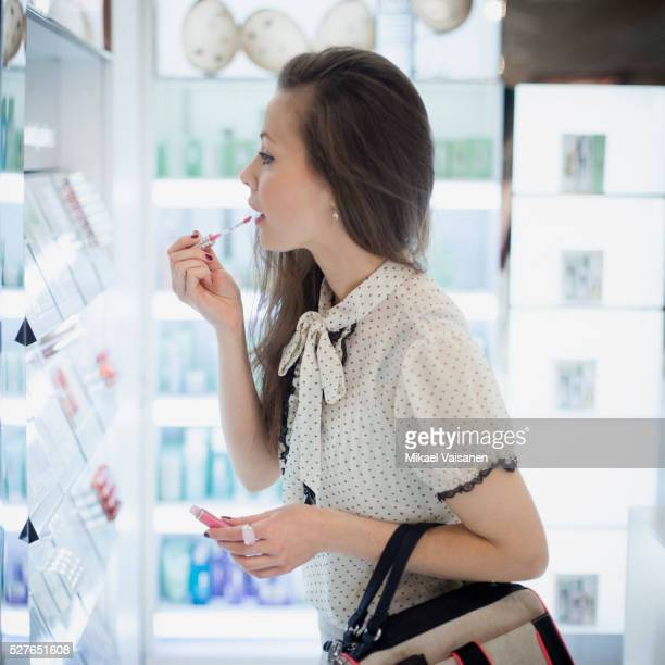 Young attractive woman testing lipstick sample