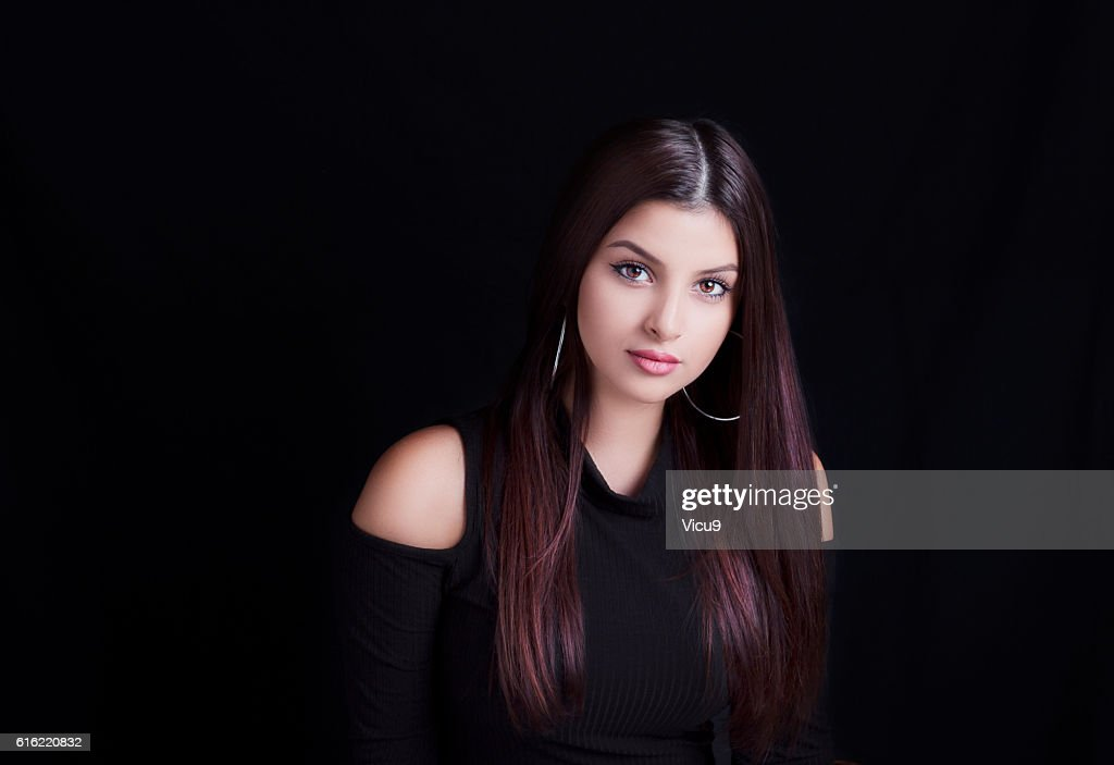 Young attractive woman with long hair on black background. : Photo
