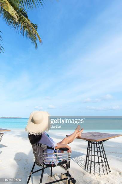 young attractive woman with straw hat enjoying her holidays at the tropical beach - liu he stock pictures, royalty-free photos & images