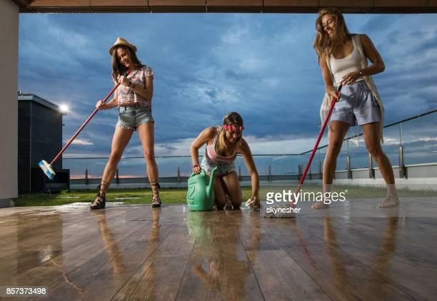 Junge attraktive Frauen, die Reinigung des Bodens auf der Terrasse.