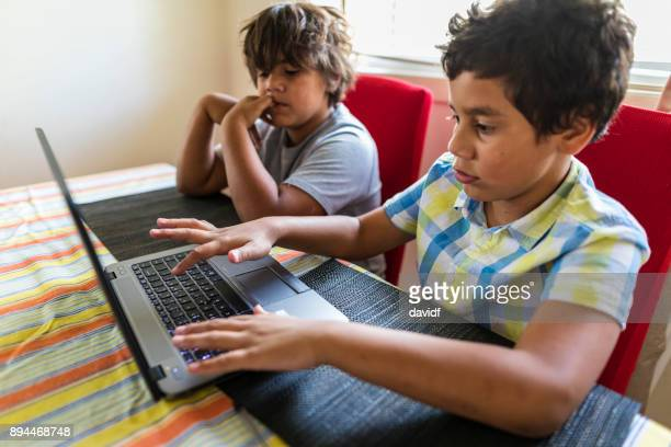 Young Australian Aboriginal Boys Having Fun Playing on a Laptop Computer