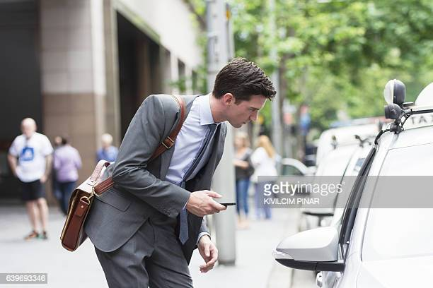 Young Australian business using taxi app