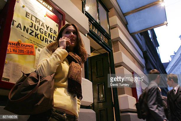 A young Austrian woman makes a cell phone call before entering the famous Elmayer School where she will learn how to waltz March 17 2005 in Vienna...