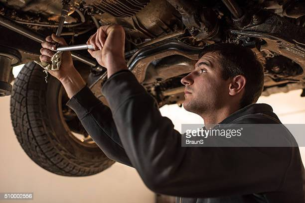 Young auto mechanic repairing chassis of a car.