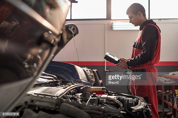 Young auto mechanic using voltmeter in a repair shop.