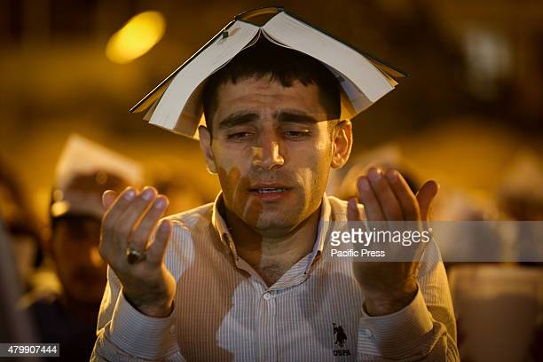A young Azerbaijani muslim boy is holding the Quran on his head while sitting with other men during Laylat Al Qadr also known as the Night of Power...
