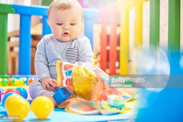 若い赤ちゃんたおもちゃで遊ぶ少年でベビーサークル